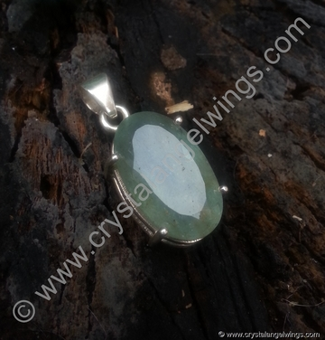 Aquamarine natural crystal pendant on tree log